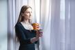 canvas print picture - Frau steht mit Kaffee allein am Fenster während der Covid-19 Ausgangssperre