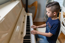 Young Boy Playing The Piano At...