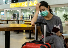 Distraught, Stressed Girl Traveler With A Medical Mask On Her Face Is Waiting For Missed, Delayed Or Canceled Flight Due To A Coronavirus.