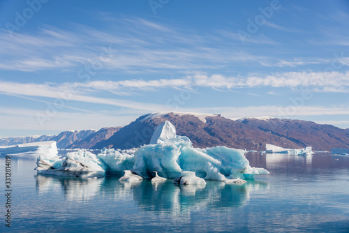 Iceberg in Greenland fjord with reflection in calm water Canvas Print