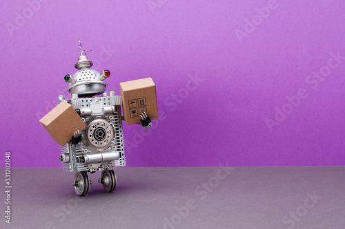 Obraz A two-wheeled robot courier is holding parcels cardboard boxes. The concept of fast automated delivery of goods, products and food using robotic autonomous vehicles. purple background, copy space - fototapety do salonu