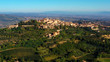 Drone flying over a magnificent authentic Italian cityscape and green meadows. Aerial view of the beautiful medieval old town of Montepulciano with red roofs Tuscany, Italy