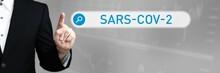 SARS-CoV-2. Mann Im Anzug Zeigt Mit Dem Finger Auf Ein Suchfeld. Das Wort SARS-CoV-2 Steht In Der Suche. Symbol Für Business, Finanzen, Statistik, Analyse, Wirtschaft