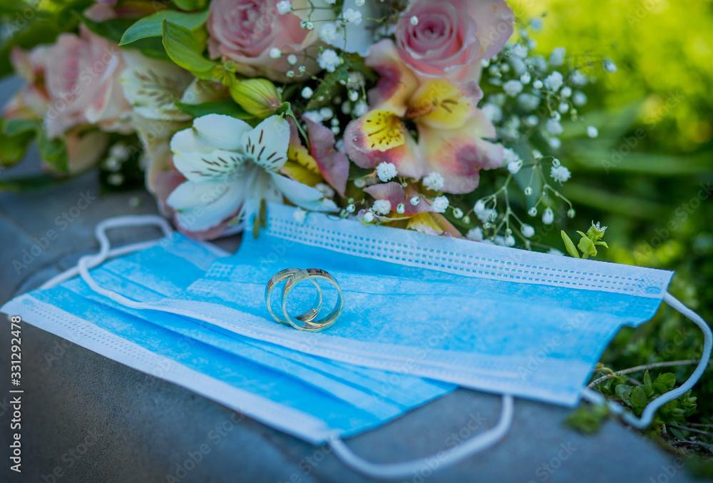 Fototapeta Two wedding rings lie on medical masks on the background of a wedding bouquet. Quarantine Wedding, Coronovirus