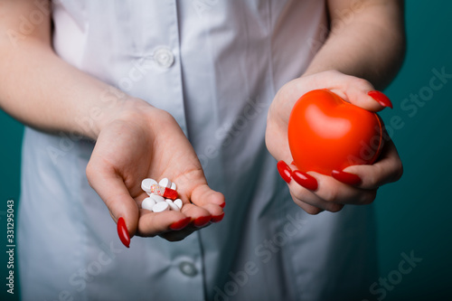 Photo An approximate shot is a hand with pills and medicines, in the other hand a red healthy heart