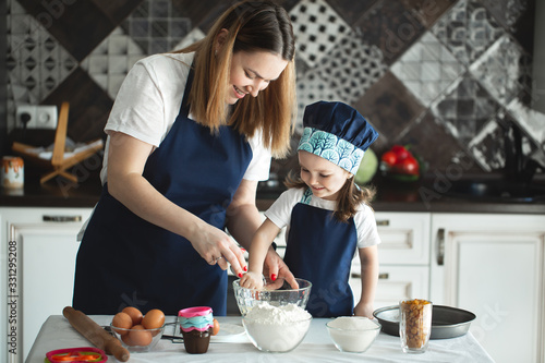 Mother and daughter preparing a sweet cake using flour, milk, sitting on chairs at a table in a modern kitchen Fototapet