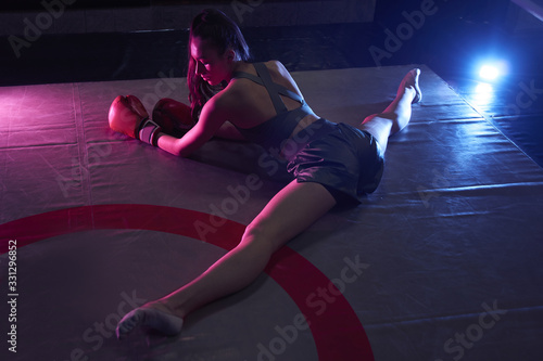 obraz PCV Young sexy girl in boxing gloves and sportswear doing stretching in the ring, sitting on a twine in neon light