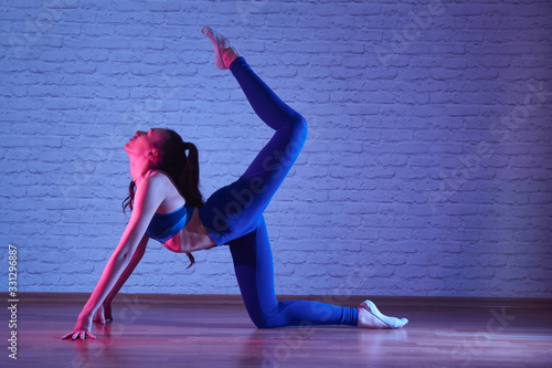 obraz PCV Flexible plastic girl doing exercises in sportswear in yoga studio, body stretching pose in neon light, Pilates