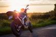 Błękitny motocykl na tle zachodzącego Słońca