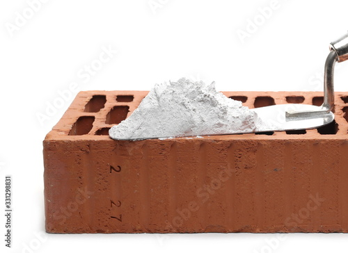 Photo Metal trowel with cement and red brick isolated on white background