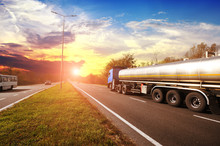 Big Metal Fuel Tanker Truck Shipping Fuel With Other Cars On The Countryside Road With Trees Against A Sky With A Sunset
