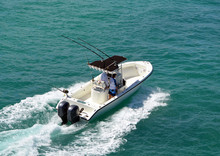 Angled Overhead View Of An Open Sport Fishing Boat With A Black Canvas Canopied Center Console Powered By Two Outboard Meninges.
