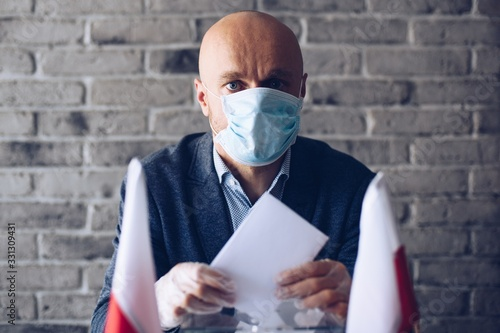 Fotografie, Obraz Man in medical mask putting his vote to voting ballot box.