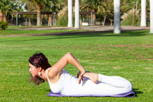 Flexible Yogi Lying On Green Grass Practicing Bhekasana On Sunny Morning At Park. Young Woman With Red Streaks And White Outfit Doing Frog Yoga Pose On Natural Environment. Flexibility Concept