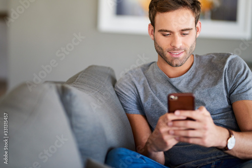 Obraz Smiling young man texting on his living room sofa - fototapety do salonu