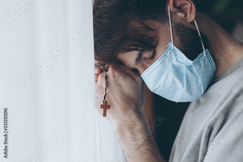 Photo a prayer on the rosary of a mortally ill young man who has lost hope in healing