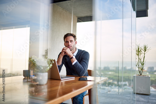 Young businessman deep in thought while working from home Fototapete