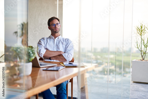 Fototapeta Young businessman deep in thought while working at a table