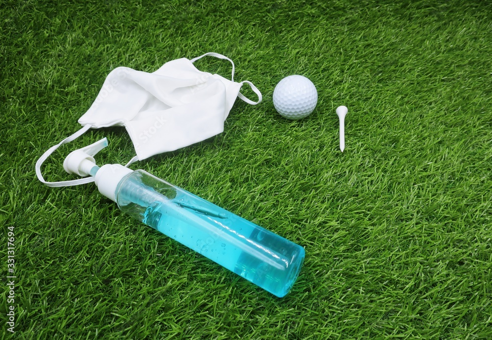 Fototapeta Golfer is preparing hand gel face mask golf ball and tee before go to play golf to prevent corona virus