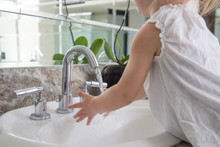 Handwashing - Adorable 2 Years Old Caucasian Girl Washing Her Hands In The Bathroom Sink. Handwashing Can Become A Lifelong Healthy Habit If You Start Teaching It At An Early Age.