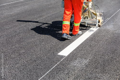 Fototapeta Road workers use hot-melt scribing machines to painting dividing line on asphalt road surface in the city
