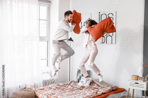 Obraz Happy young couple fighting on pillows in bedroom - fototapety do salonu