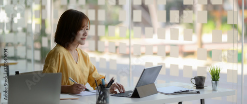 Fototapeta Cropped shot of female entrepreneur focusing on her work in glass wall office obraz