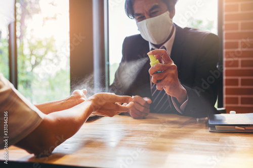 Fotografía Businessman with mask applying alcohol spray for cleaning and protecting colleag