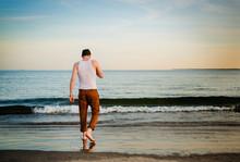 Man Walking On The Beach At Su...