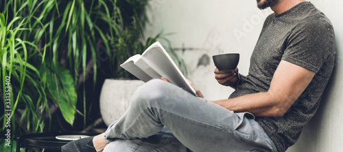 Fototapeta Handsome hipster man relaxing read the paper book work study and looking at page