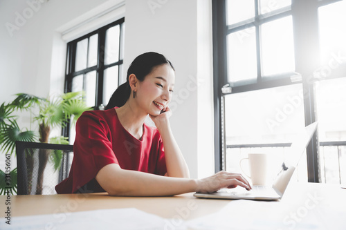Fototapeta Portrait of beautiful young asian woman working on laptop in workplace obraz