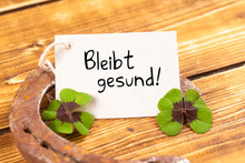 Horseshoe With Green Shamrock And German Text Bleibt Gesund, In English Stay Healthy