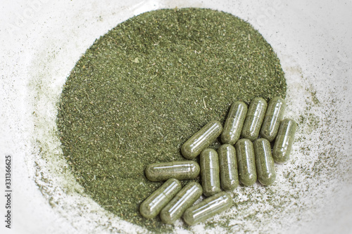 Green andrographis paniculata powder and capsule, a Thai traditional herb and has antipyretic properties close-up Canvas Print