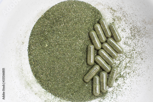 Photo Green andrographis paniculata powder and capsule, a Thai traditional herb and has antipyretic properties close-up