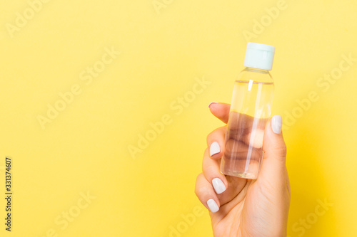 Female hand holding cosmetics bottle at yellow background with empty space for y Fototapet