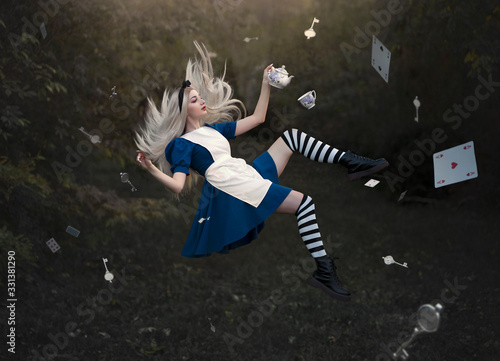 A beautiful blond girl is levitate with a mug of tea above the ground Wallpaper Mural