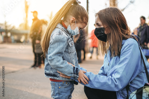 Fényképezés A girl with a child is standing on the road in a protective medical mask