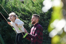 Bearded Man Pushing A Blonde Child On A Swing With White Sweater