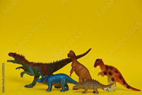a group of toy dinosaurs walk on a yellow background