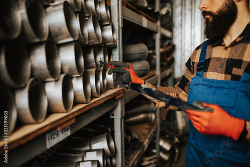 Obraz Handsome adult man working in car and truck spare parts warehouse. - fototapety do salonu