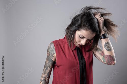 Obraz na plátně Ragazza mora con una camicia smanicata rossa e una cravatta nera, piena di tattu