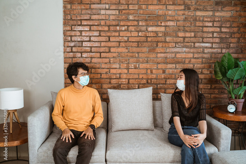 Foto Man and woman wear face masks, sit apart, social distancing