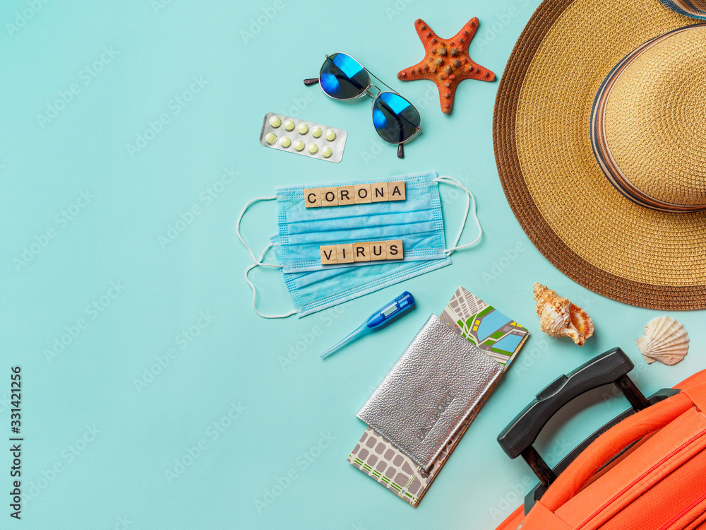 Fototapeta Coronavirus covid-19 and travel concept. Summer vacation and beach rest symbols and breathing mask on blue background. Flat lay or top view. Copy space for text or design.