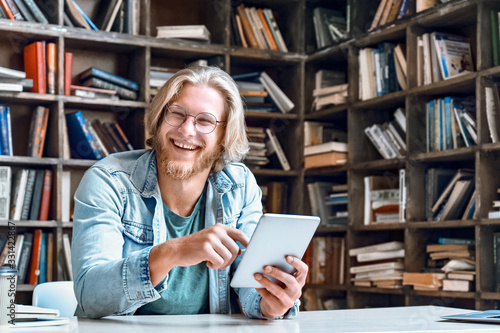 Happy male student teacher smiling laughing holding using digital tablet computer looking at camera e learning easy internet course study online in app concept with device sit at library desk Canvas Print