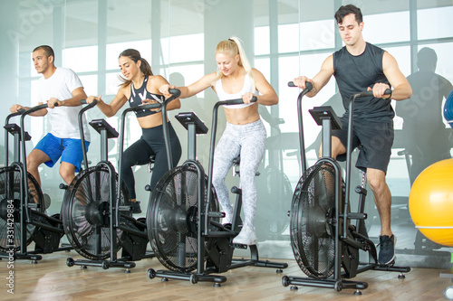 Obraz Group of young people doing exercises on elliptical machine at gym - fototapety do salonu