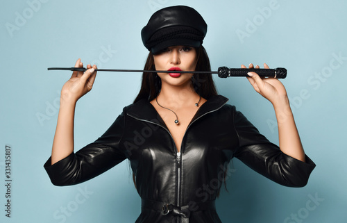Fotografia, Obraz Young beautiful sexy brunette woman in stylish black leather dress and hat stand