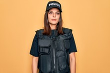 Young Beautiful Brunette Policewoman Wearing Police Uniform Bulletproof And Cap Relaxed With Serious Expression On Face. Simple And Natural Looking At The Camera.