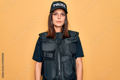 Fototapeta Young beautiful brunette policewoman wearing police uniform bulletproof and cap Relaxed with serious expression on face