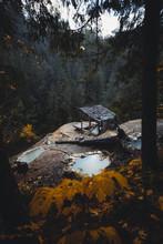Heiße Quelle Mit Kleiner Holzhütte Und Herbstlaub Im Vordergrund Sowie Baumstämmen Und  Nebel Im Hintergrund