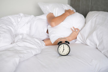 Woman sleep on the bed turns off the alarm clock wake up at the morning, Selective focus..